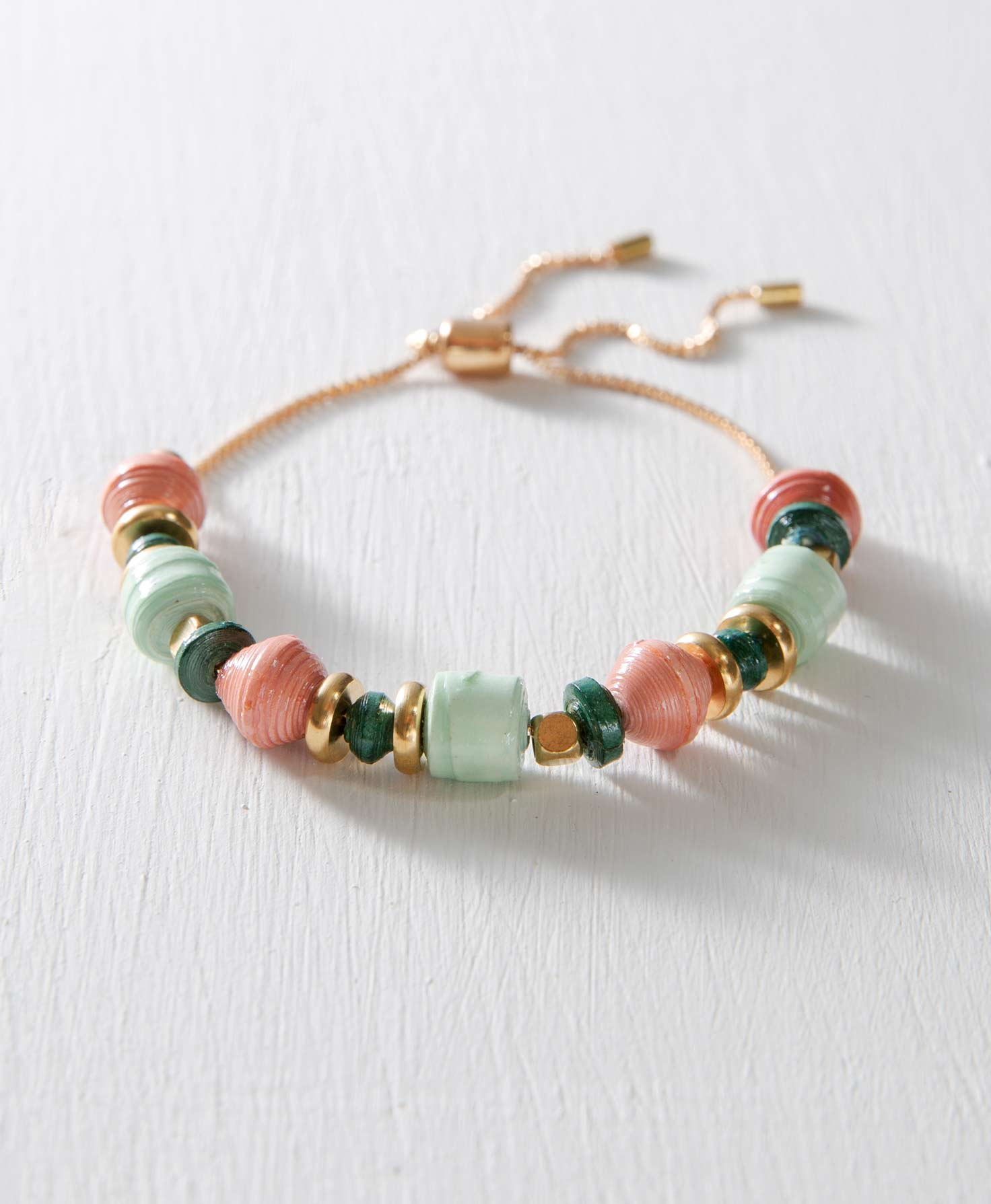 The Posy Bracelet features hand-rolled paper beads in light pink, mint green, and teal shades. Arranged in between the paper beads are cube-shaped brass beads and flat, circular brass beads. At the back of the bracelet, the beaded portion connects to a dainty brass chain with a brass bead. The chain can be adjusted for size by pulling on both ends of the chain.