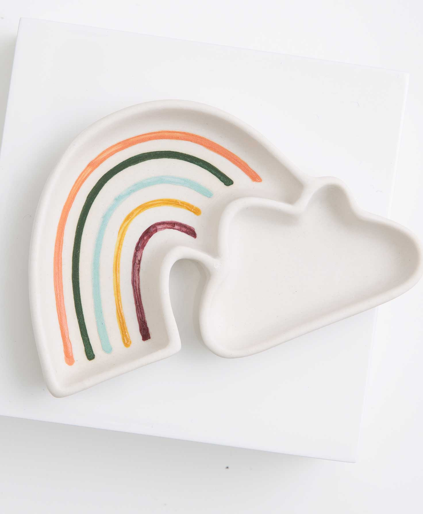 The Rainbow Trinket Tray rests on a white background. It is a flat, white ceramic tray. It is shaped like a rainbow with a cloud on one end. The rainbow and the cloud form two distinct compartments of the tray. There is a raised lip around the entire tray to keep items inside. Inside the rainbow section of the tray there are colorful stripes in shades of orange, forest green, sky blue, yellow, and pink to represent the colors of the rainbow. The inside of the cloud section has no markings.