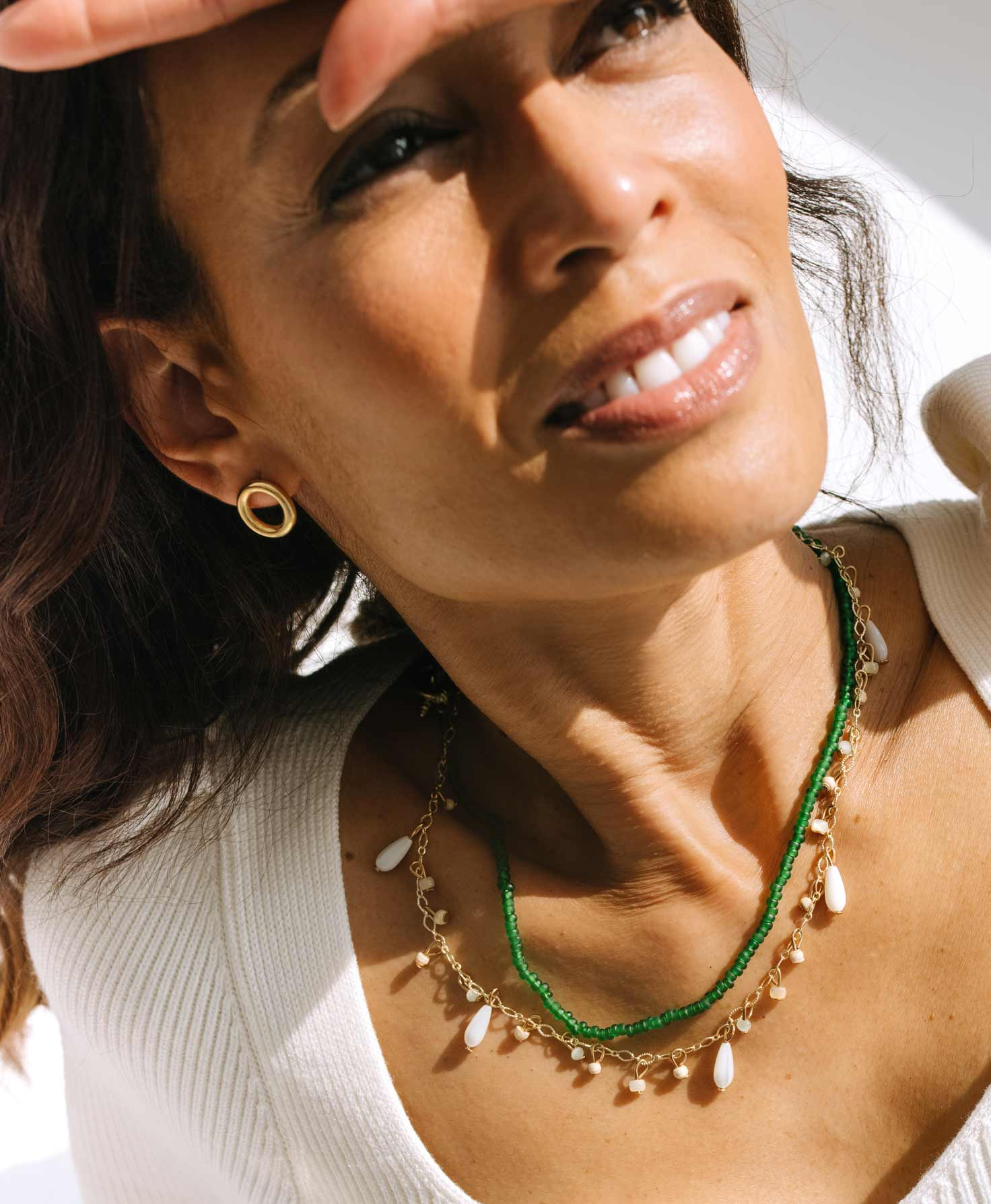 A model wears the Revolve Earrings with a neutral white top. She also wears the gold and white Shipshape Necklace and the Fern Necklace, which brings a pop of color to the neutral look.