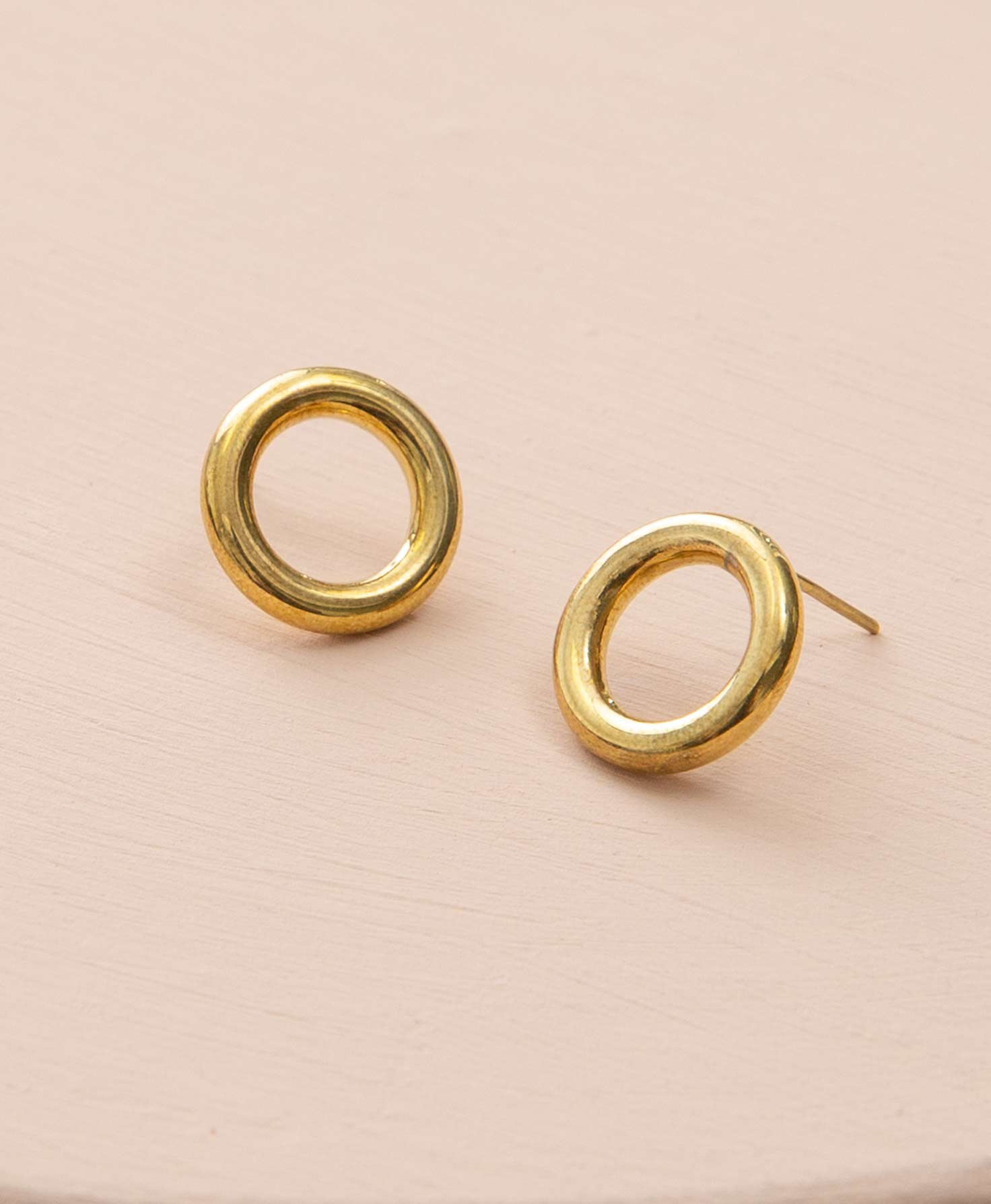 The Revolve Earrings sit propped up on a blush-colored platform. They are stud-style earrings made of shining gold plated brass. A brass tube wraps around to form a perfect circle that is open in the middle. The earrings resemble dainty gold doughnuts.