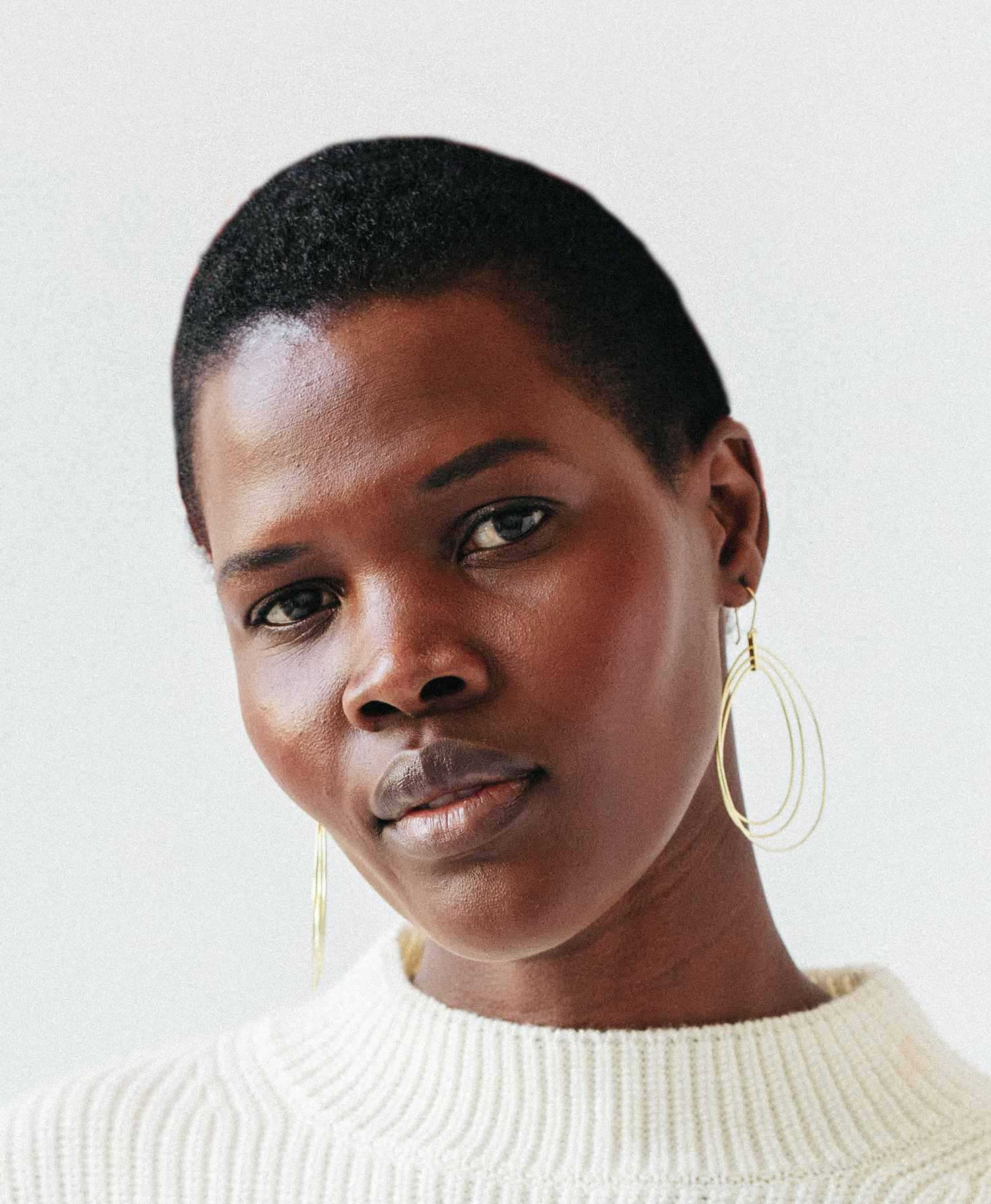 A model wears the large Satellite Earrings, which hang down several inches and sparkle in the light. Paired with her white turtleneck sweater, they add some modern shine to her look.