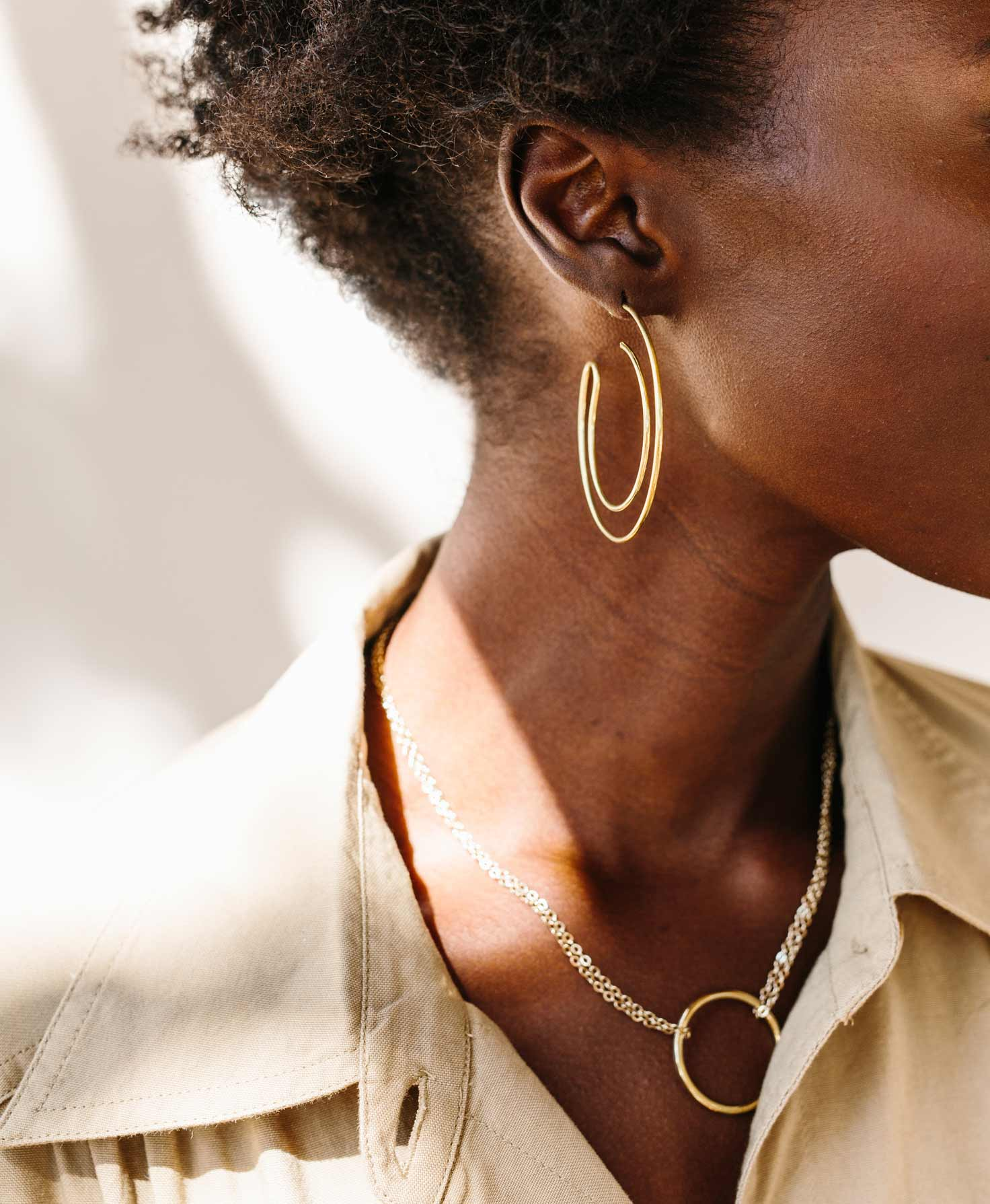 A model wears a beige blouse. She also wears the Halcyon Necklace with the brass Serendipity Earrings for a classic, neutral feel.