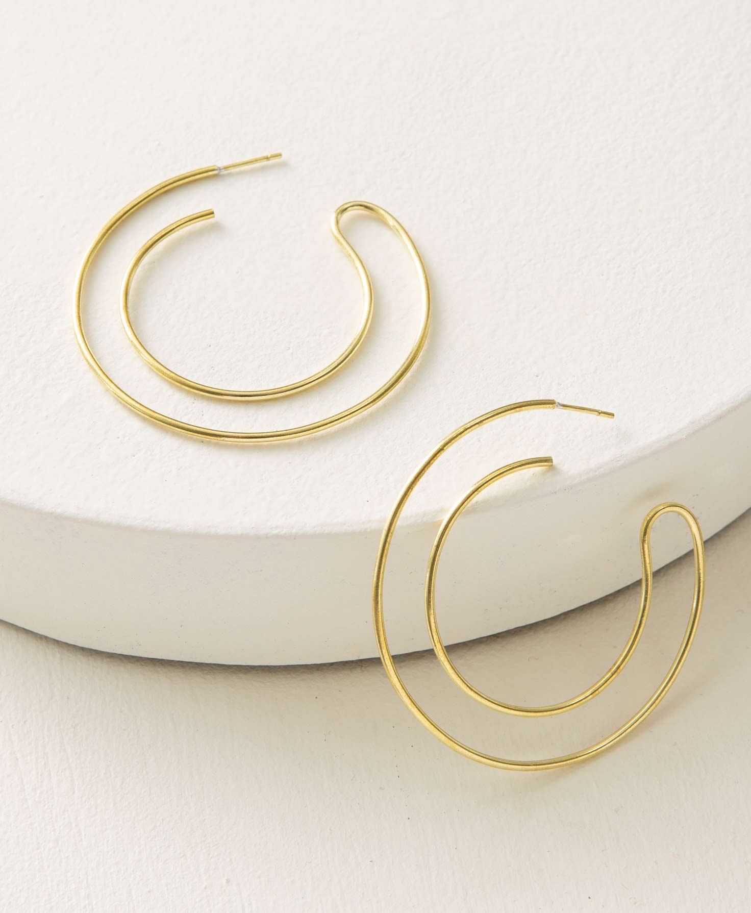 The Serendipity Hoops rest on a white platform. The earrings have a double hoop design, but are composed of only one thin brass tube curved in on itself. The brass tube curves down and around in a classic hoop shape, then curves up and back around toward the ear post, forming a smaller hoop shape within the first hoop. The earrings have a shiny finish and a modern, lightweight look.