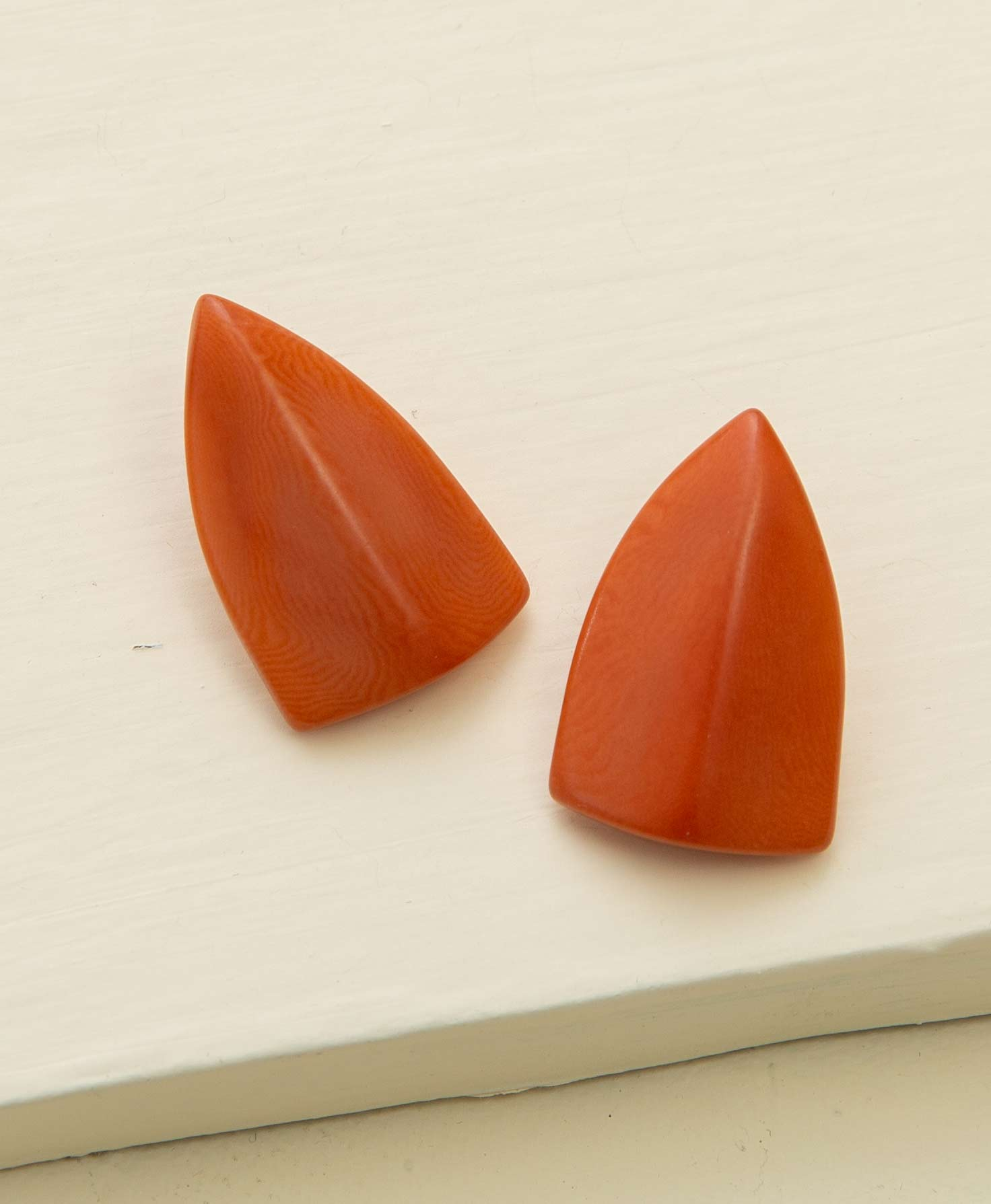 The Shield Earrings lay on a white platform. They are made from smooth carved tagua seed in a burnt orange shade. The seed is carved into a shield-like shape that comes to a point at the top of the earring.