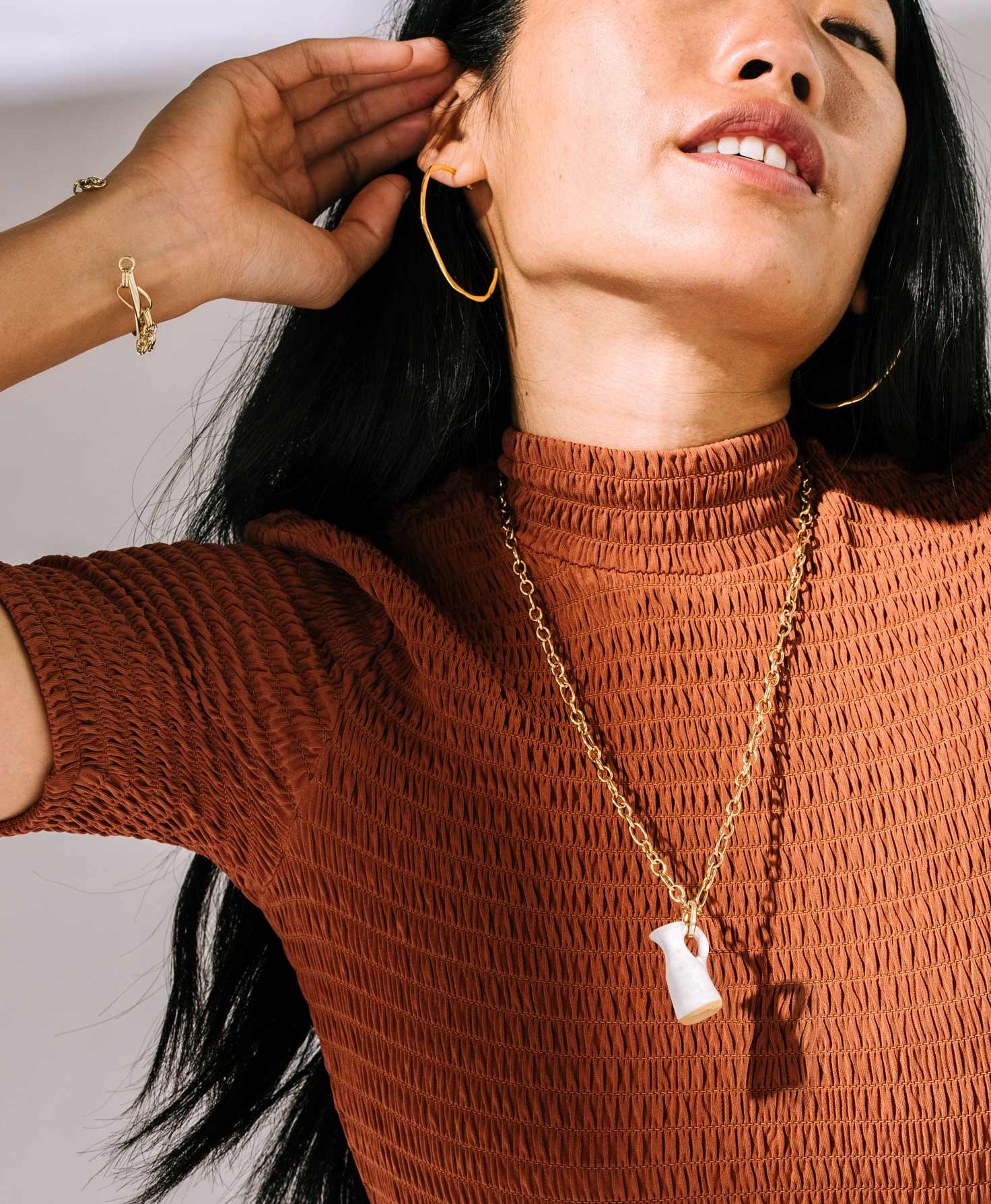 A model wears the Shindig Bracelet. It shines as it catches the light. She also wears the Signal Hoops and Petite Pitcher Necklace, which share the bracelet's neutral gold color palette.