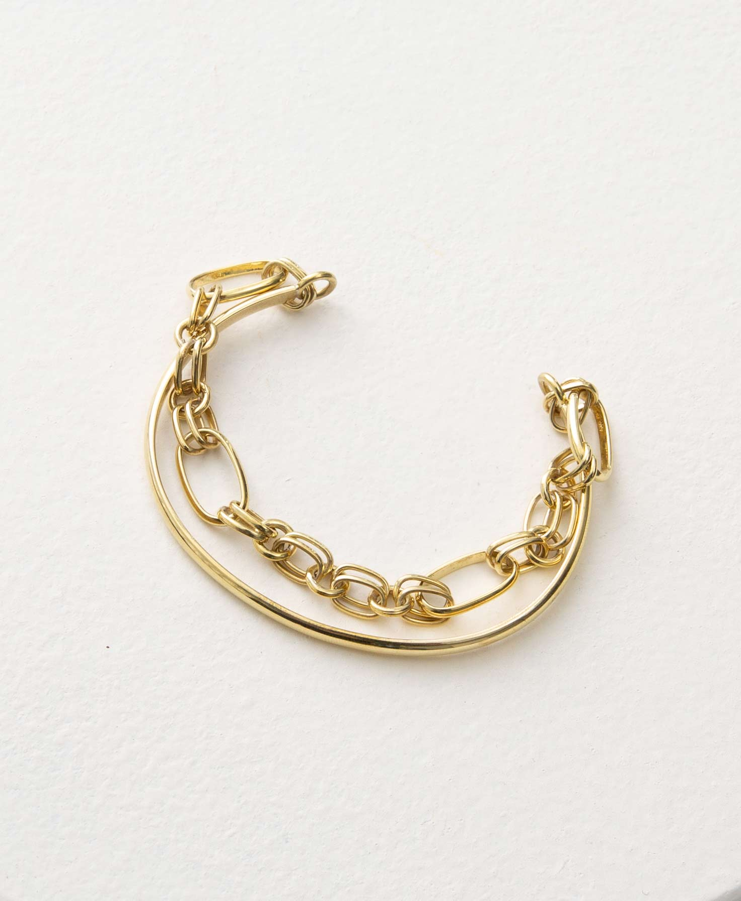 The Shindig Bracelet sits on a white platform. It is made of shining brass. It is a cuff-style bracelet with an opening in the back where it can be slid onto the wrist. A thin brass cuff is layered beneath a chunky brass chain with circular and oval-shaped links. This gives the bracelet a 2-in-1 appearance.
