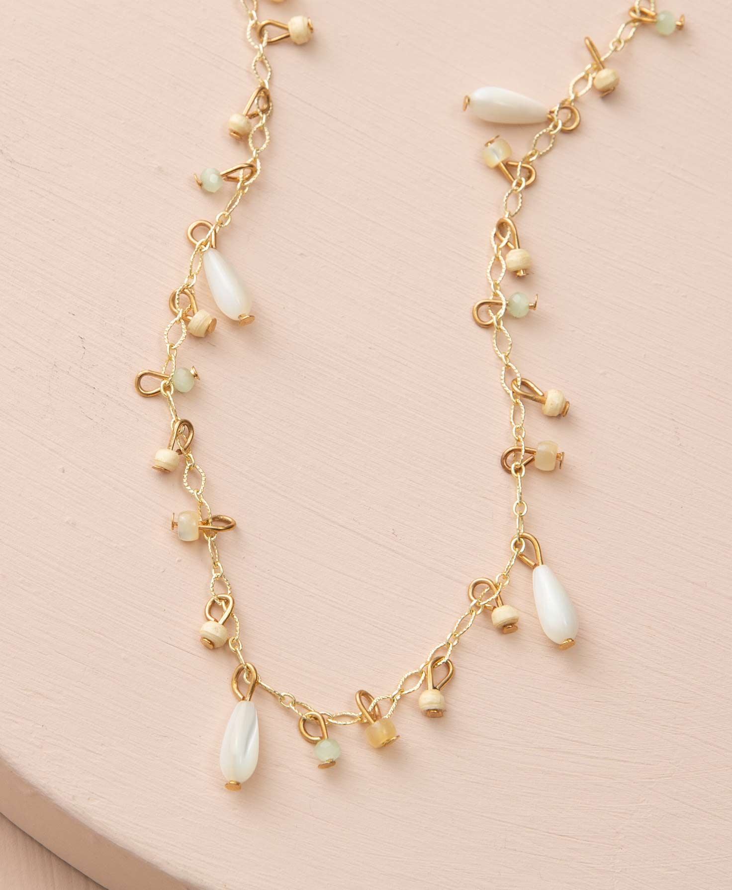 The Shipshape Necklace lays on a blush-colored platform. It has a gold chain with medium-sized links. Every inch or so, a brass wire connects a bead to the chain. Most of the beads are small, round paper or glass beads. They are either cream or mint colored. Every few inches there is a larger, teardrop-shaped pearl bead connected to the chain.
