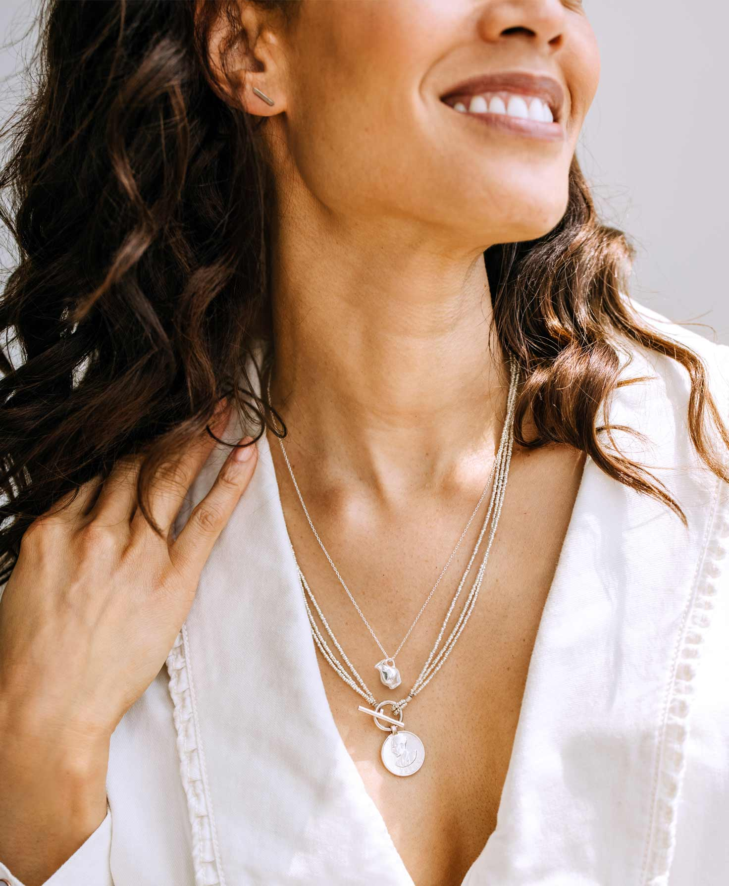 A model wears the dainty Silver Bar Studs. She also wears two silver metallic necklaces layered together: the Fount Necklace and the Artillery Treasure Necklace.