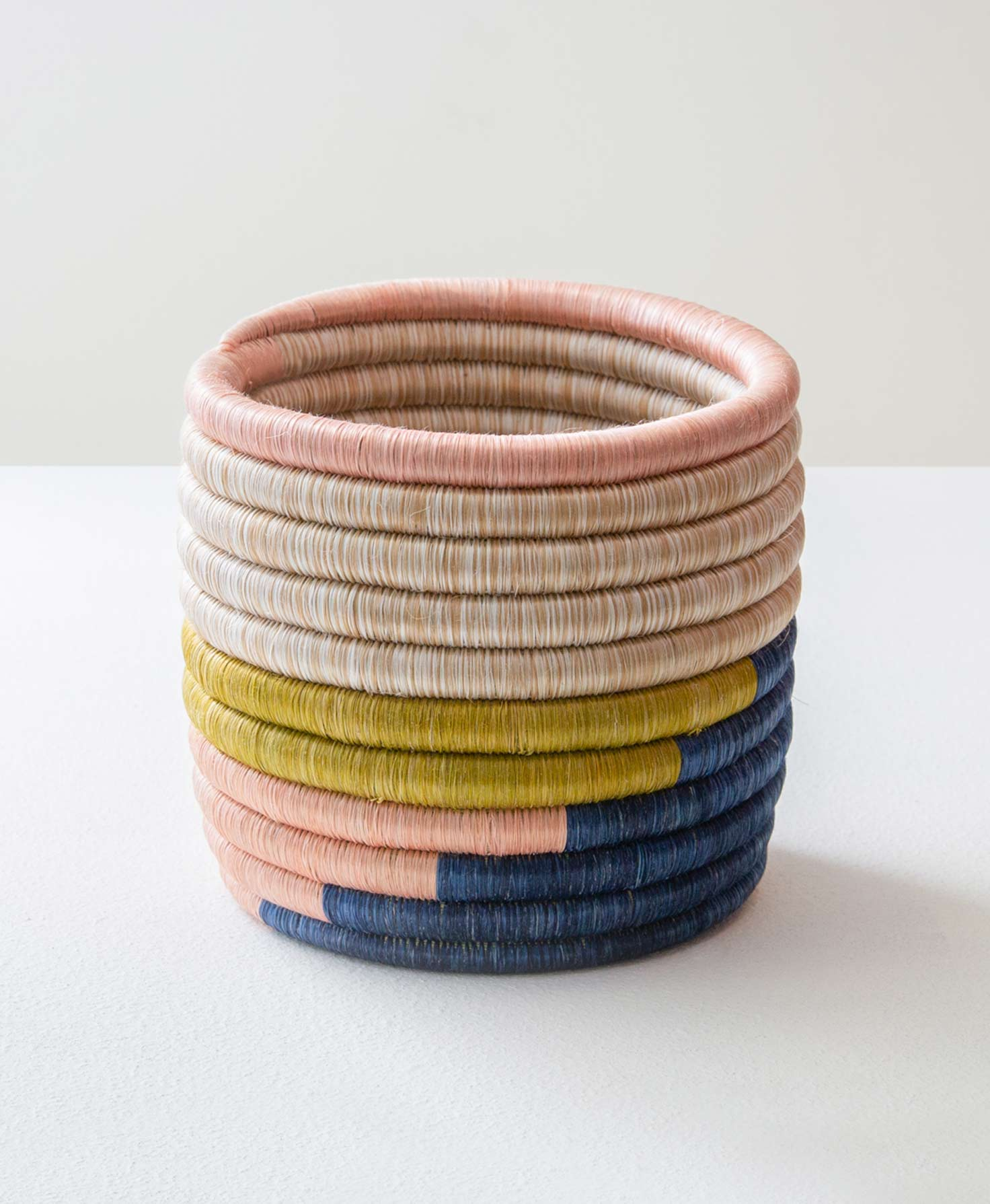The Sisal Plant Holder sits on a white surface. It is shaped like a cylinder with a flat, round base. The walls of the plant holder are made of a long, coiled tube that is wrapped in sisal grass. On the bottom half of the holder the grass is dyed navy, pink and mustard to create a color blocked look. The grass on the top half of the holder is a tan color, and the grass around the rim is pink.