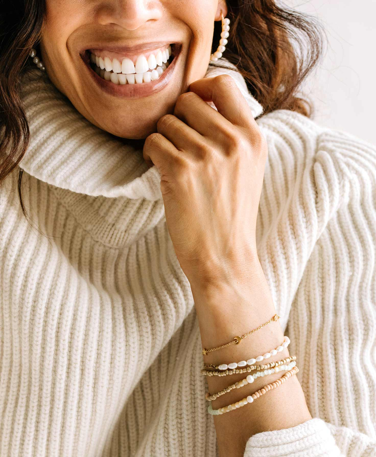 A model wears the Splendid Bracelet layered with a stack of other bracelets featuring gold metal and a soft color palette. She finishes her look with the gold and pearl League Earrings.