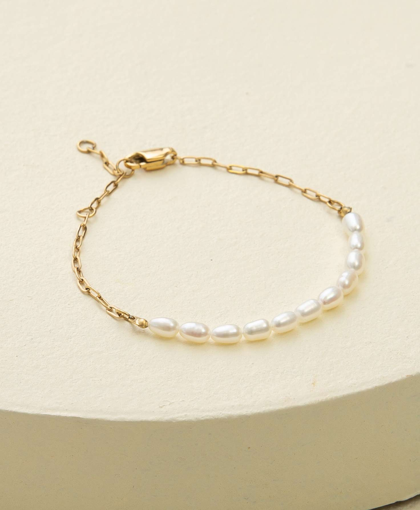 The Splendid Bracelet lays on a cream-colored block. It has a shiny gold chain made of oval-shaped links. At the front of the bracelet, the chain meets a row of 11 shining, oval-shaped pearls. A lobster-claw clasp secures the bracelet.