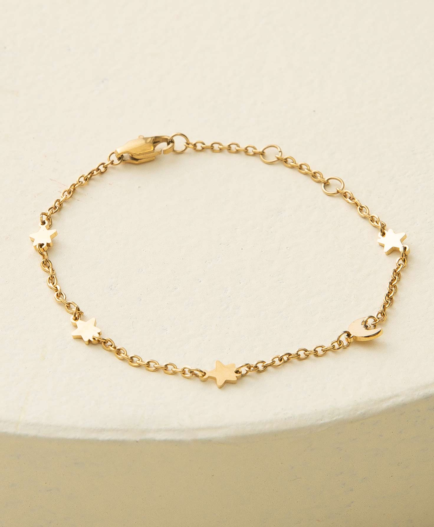 The Stargazer Bracelet rests on a white platform. It has a dainty, shiny gold chain. Small gold charms are attached to the chain roughly an inch apart. There are four star charms and one crescent moon charm. A lobster-claw closure secures the bracelet.