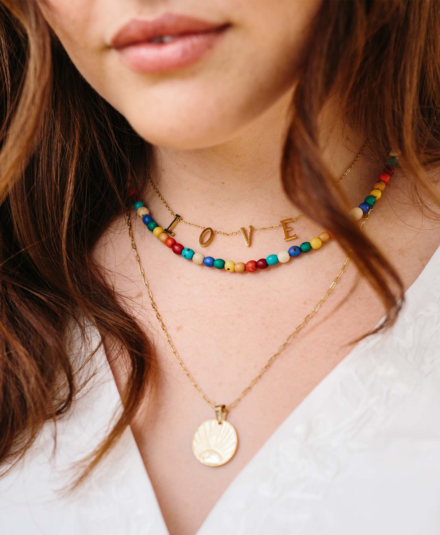 A model wears the Sunrise Necklace layered with two other necklaces. The Sunrise Necklace hangs down onto her chest, while the shorter Achira Multicolor Necklace and Beloved Necklace lay closer to her neck.