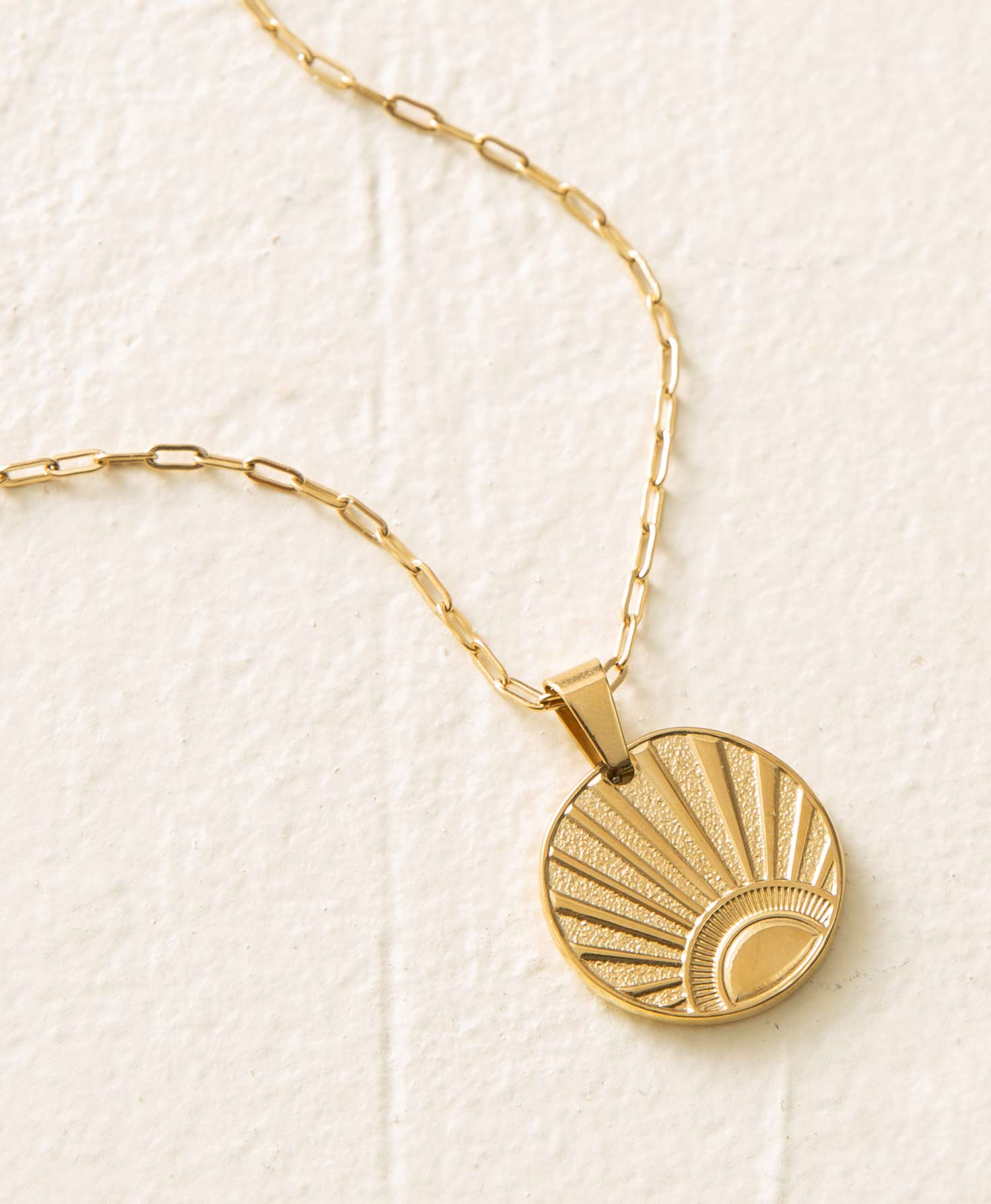 The Sunrise Necklace lays on a white background. It has a golden chain composed of elongated, oval-shaped links. Hanging from the chain is a flat, circular pendant etched with an image of half of a sun emerging over the horizon and emitting bright rays of light across the pendant. Both the chain and pendant have a glossy metallic finish.