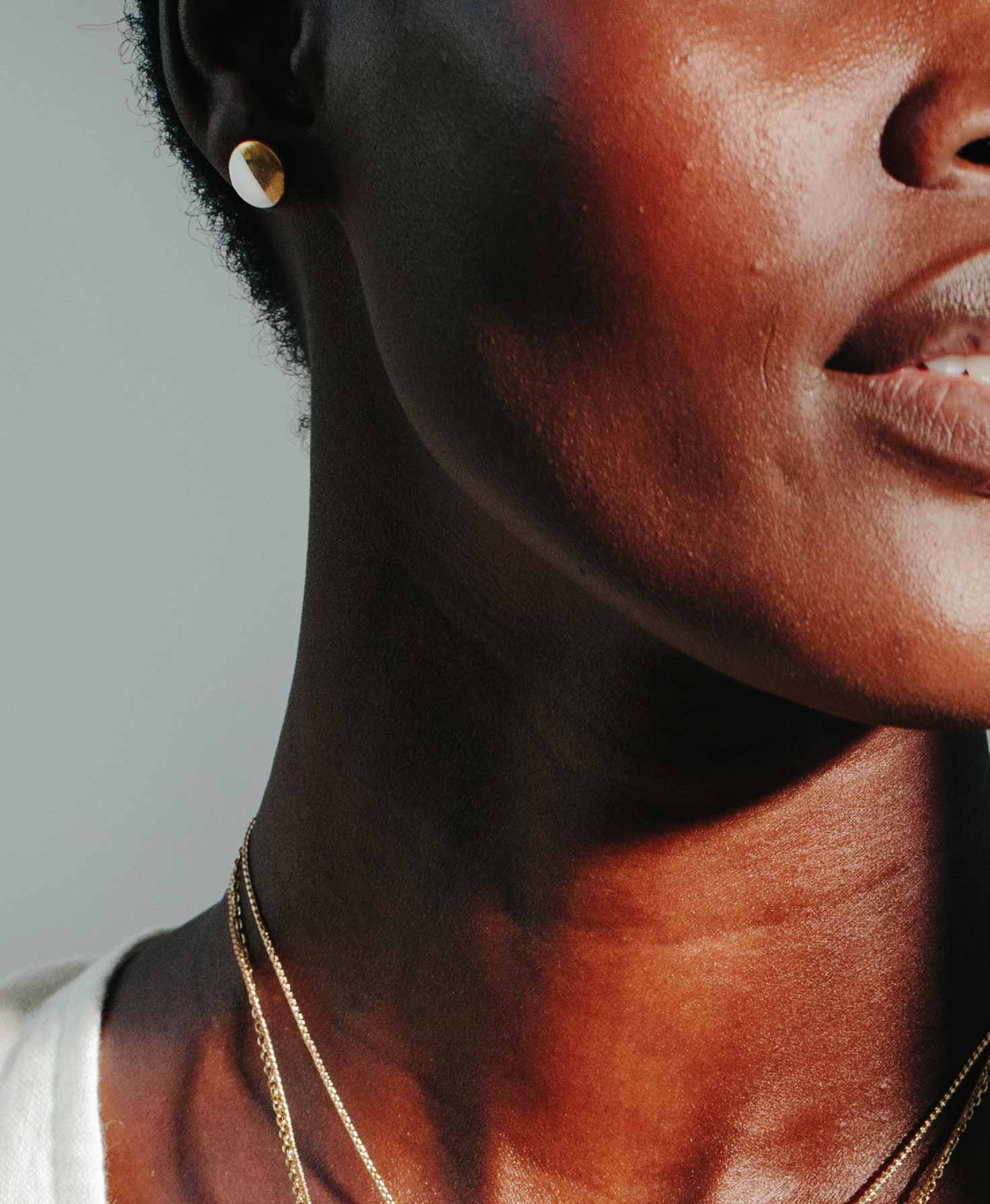 A model wears the Sweet Ceramic Studs, which shine as they catch the light. She also wears two dainty gold necklaces to complete the metallic look.
