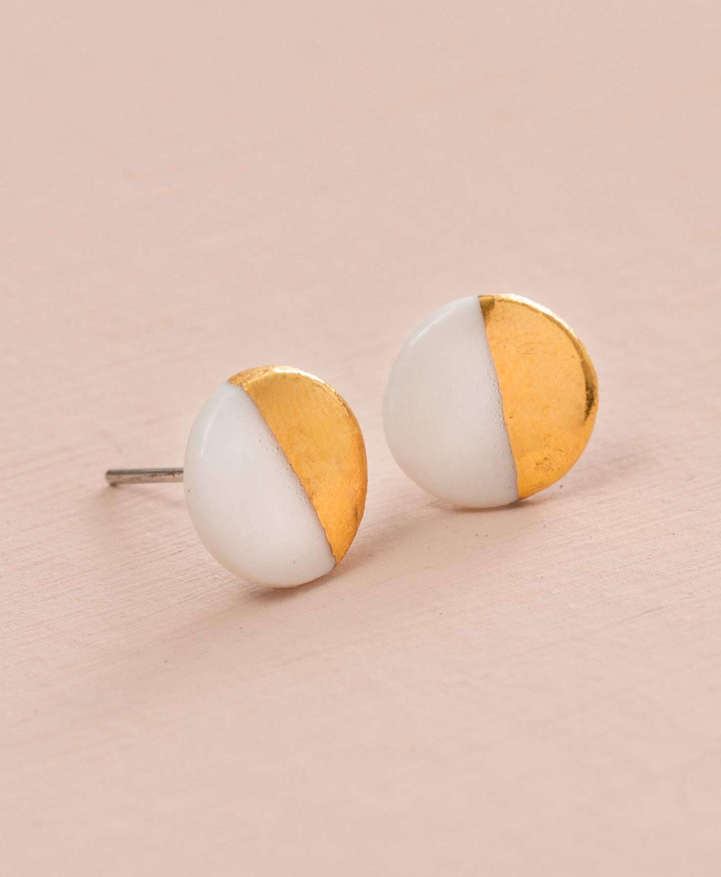 The Sweet Ceramic Studs rest on a blush colored background. They are post-style earrings featuring a small, flat ceramic disc attached to the ear post. The disc is a glossy white color, and one half of it has been dipped in gleaming gold luster for a half-and-half look.