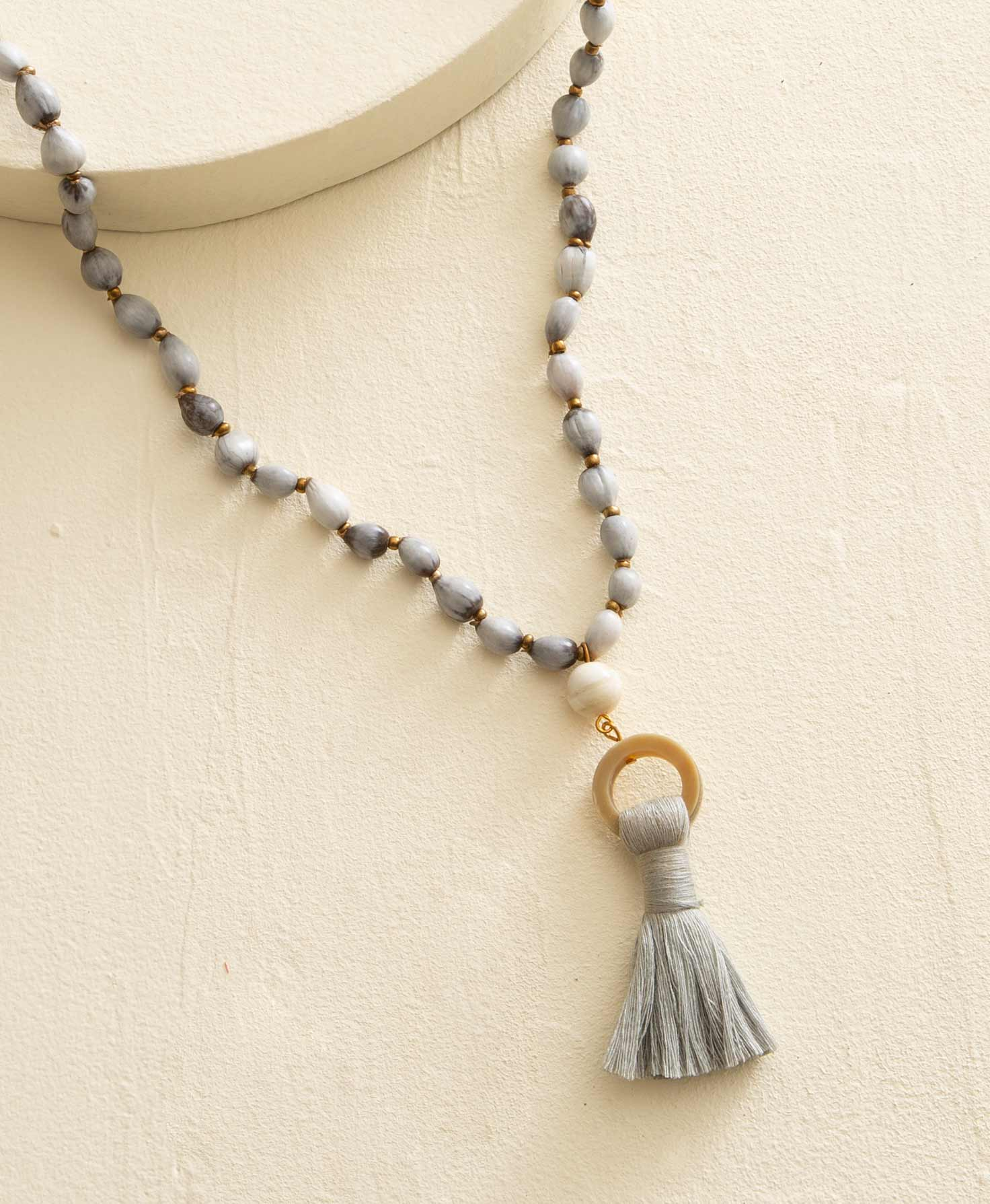 The Tempest Necklace lays draped on a cream background. It is a long rope necklace made primarily of natural embira seeds, which are smooth, light grey seeds with some dark grey striations. In between the embira seeds are small brass-colored beads. At the bottom of the necklace is a pendant composed of a caramel-colored horn hoop with a grey thread tassel hanging from the bottom.