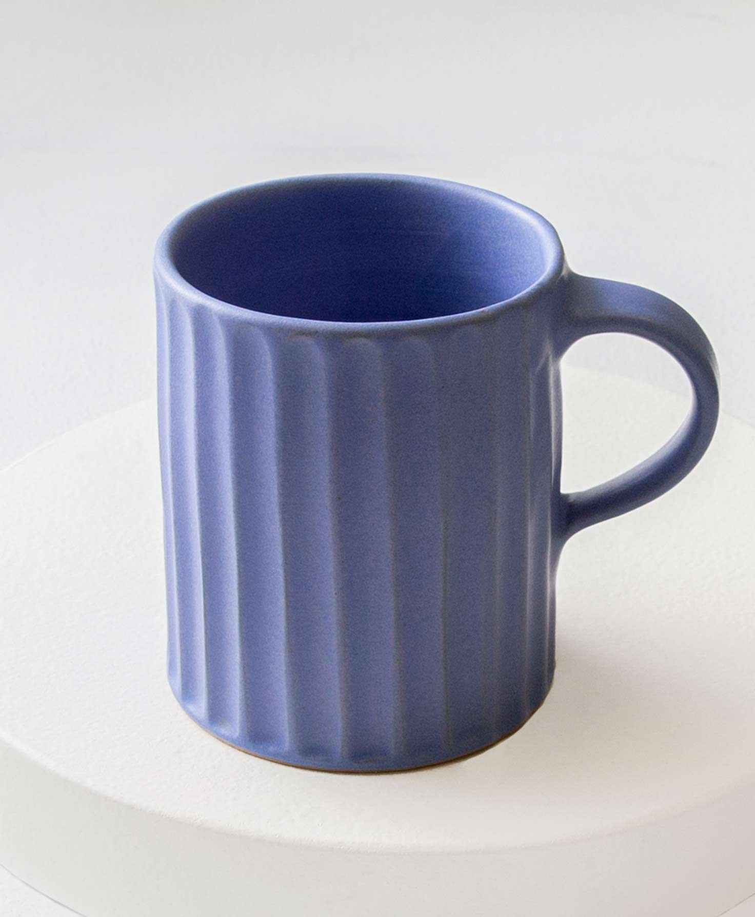 The Textured Ceramic Mug in Blue sits on a white surface. It is made of cobalt blue stoneware and has a natural, handmade texture. All the way around the mug, vertical indentations run from the top to the bottom. The effect feels like someone ran their fingers from the top of the clay to the bottom, leaving regular rows of indentations. The mug has a handle made of the same blue stoneware.