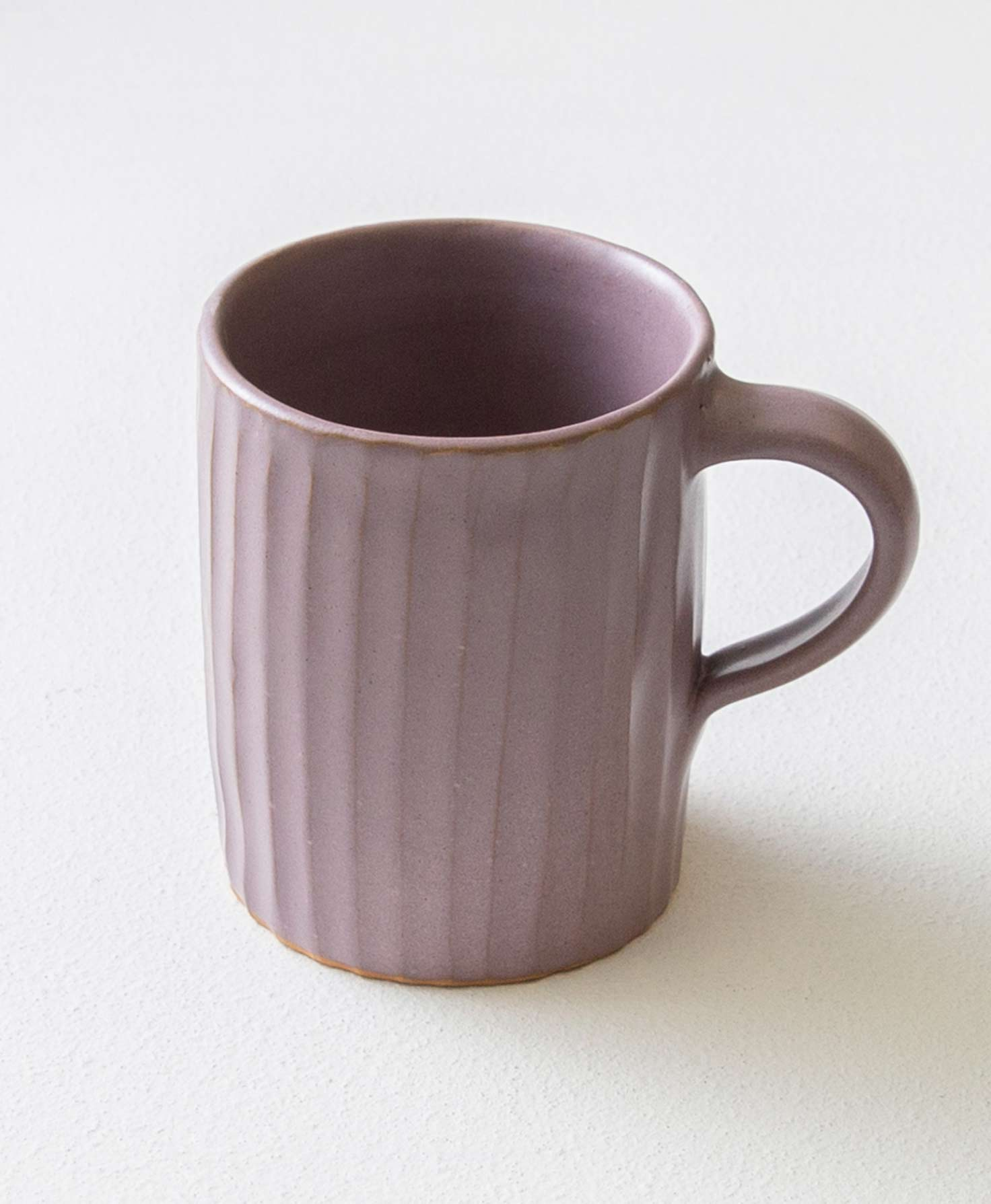 The Textured Ceramic Mug in Lilac sits on a white surface. It is made of dark lilac stoneware and has a natural, handmade texture. All the way around the mug, vertical indentations run from the top to the bottom. The effect feels like someone ran their fingers from the top of the clay to the bottom, leaving regular rows of indentations. The mug has a handle made of the same lilac stoneware.