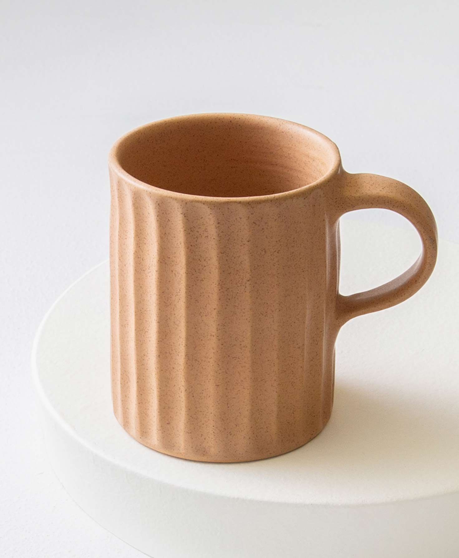 The Textured Ceramic Mug in Sand sits on a white surface. It is made of stoneware in a peachy sand shade and has a natural, handmade texture. All the way around the mug, vertical indentations run from the top to the bottom. The effect feels like someone ran their fingers from the top of the clay to the bottom, leaving regular rows of indentations. The mug has a handle made of the same peachy stoneware.