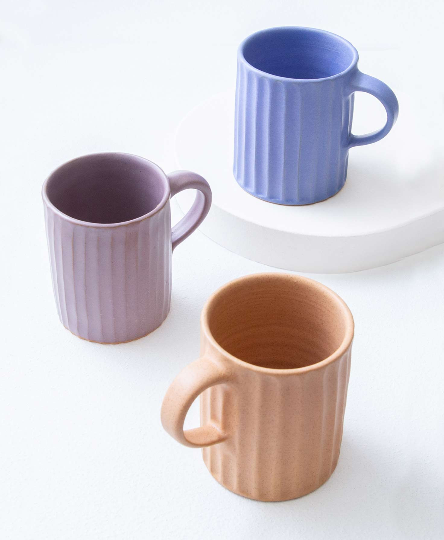 The three colors of Textured Ceramic Mugs sit together on a white surface. One mug is cobalt, one is lilac, and one is a peachy sand color. Each of the mugs has an identical shape. They are made of stoneware and have a natural, handmade texture. All the way around the mugs, vertical indentations run from the top to the bottom. The effect feels like someone ran their fingers from the top of the clay to the bottom, leaving regular rows of indentations. The mugs have handles made of stoneware that is the same color as their bodies.