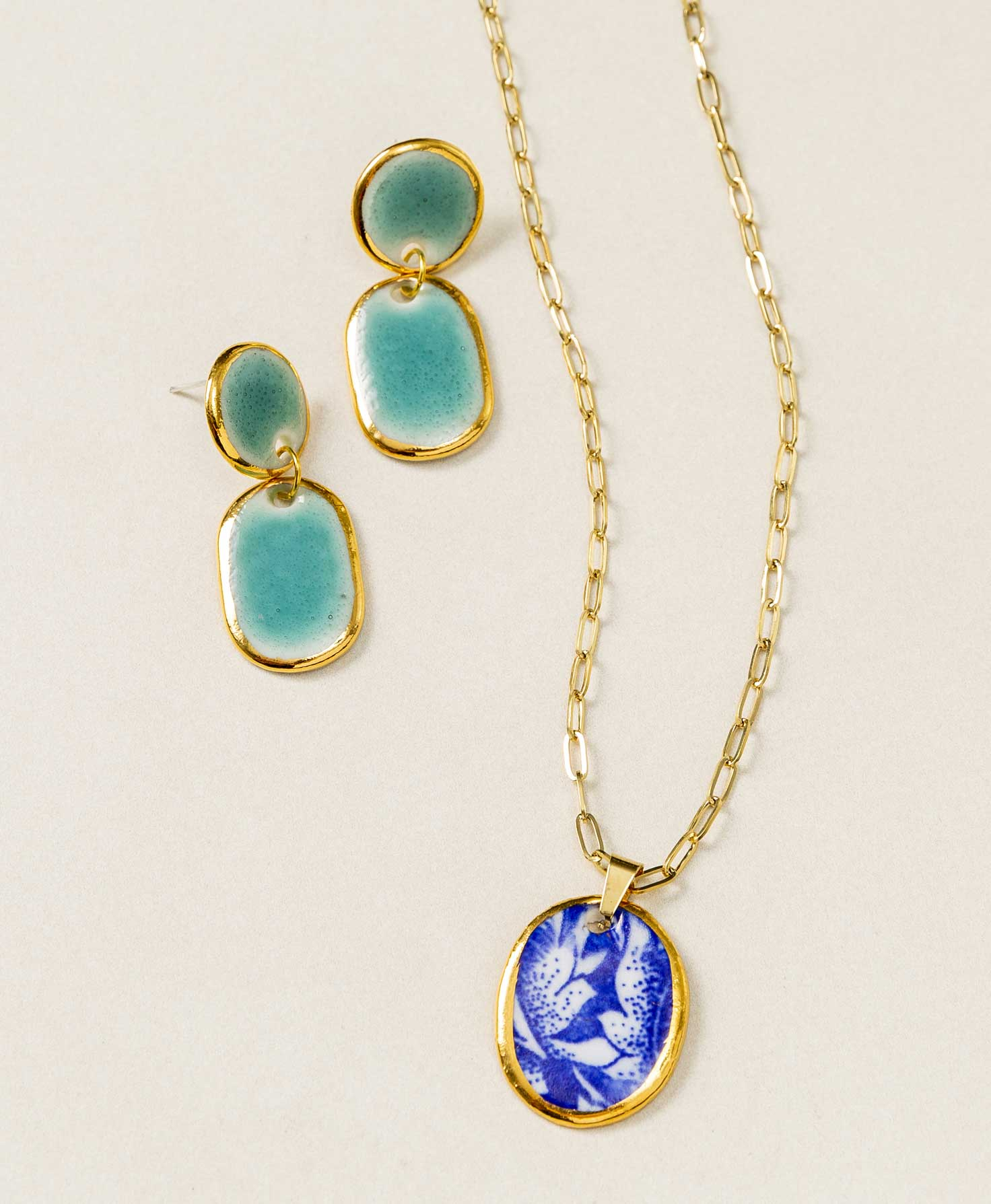 Three Thrive Necklaces lay next to each other, showing the variations in the blue and white pattern on each pendant. One necklace features a fern-like frond, and two others feature different kinds of floral imagery.