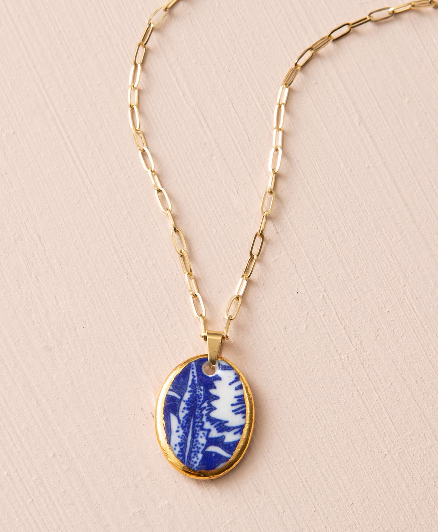 The Thrive Necklace rests on a blush colored background. It features a golden chain composed of elongated, oval-shaped links. Linked to the chain is an oval pendant composed of porcelain with a gleaming golden edge. The porcelain has a white background and a vibrant blue floral design reminiscent of classic china patterns.
