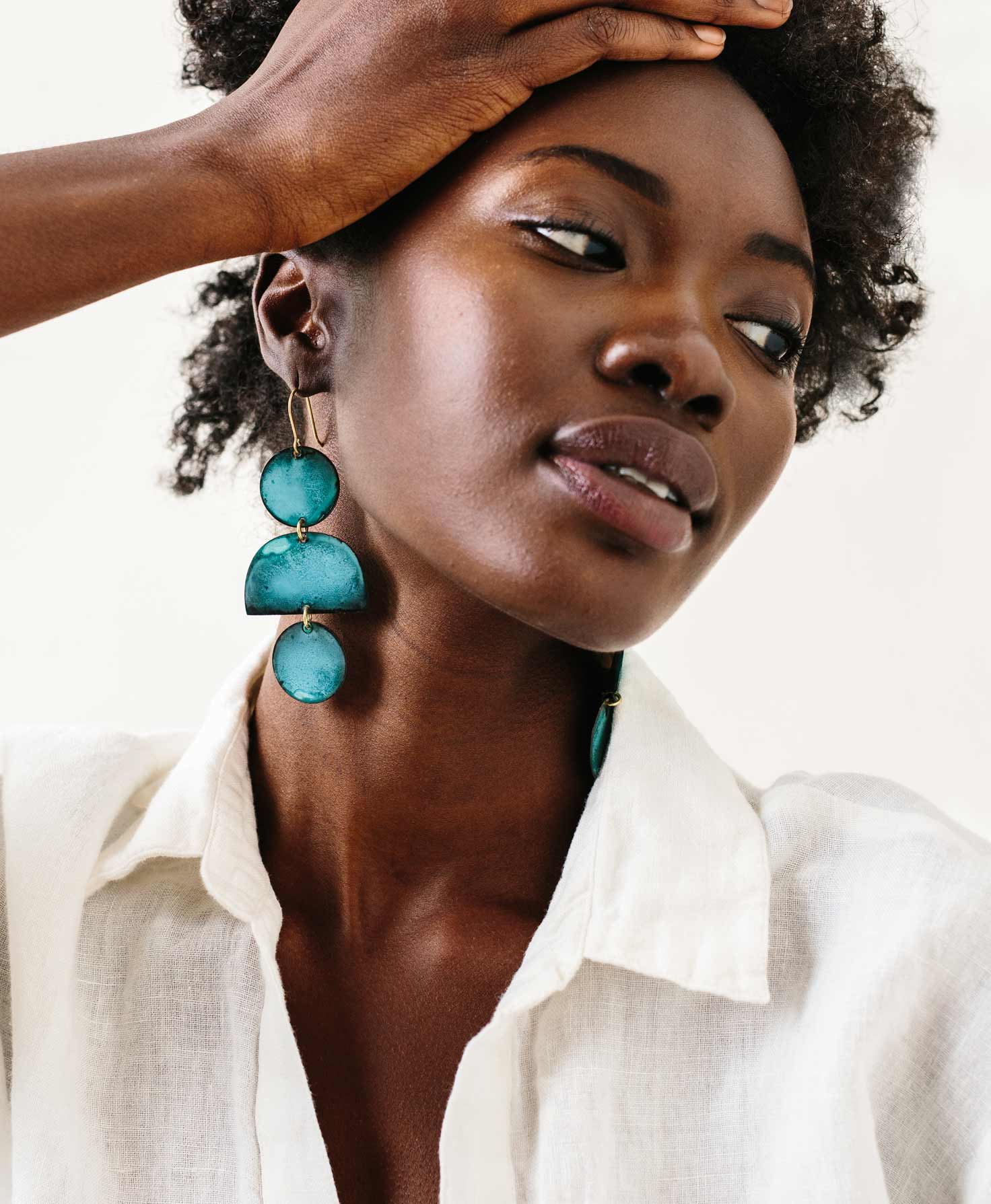 A model wears the Tide Pool Earrings with a crisp white blouse. The earrings have a rich teal color that makes a bold statement.