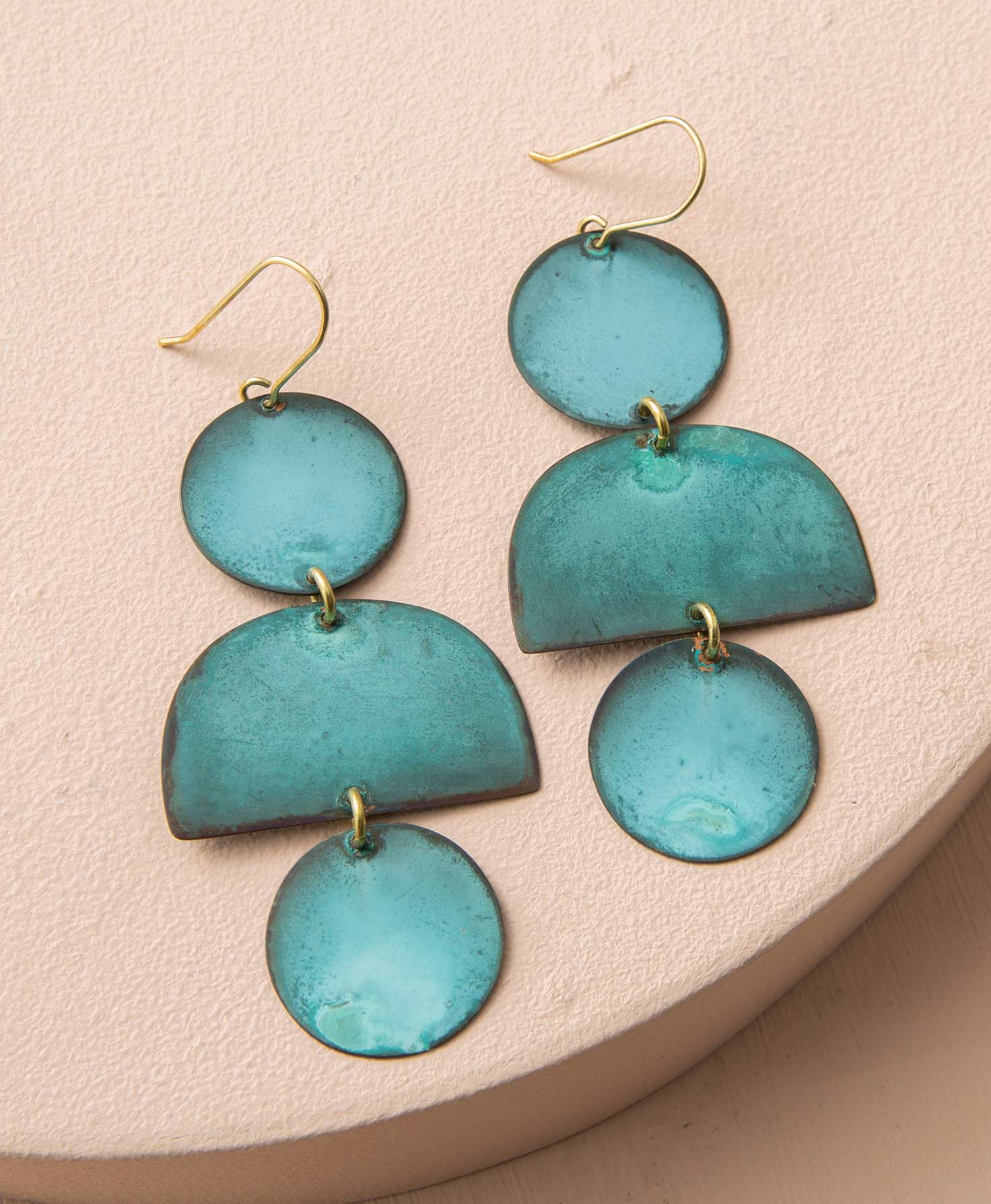 The Tide Pool Earrings sit on a blush colored block. They feature flat geometric shapes cut from copper that hang down from a gold ear hook. The copper has been patinated, giving it a vibrant teal hue with natural metallic variations. At the top of the earring is a circle shape. Connected to this is a semi-circle with its flat side facing down. Finally, at the bottom of the earring is a circle identical to the first.