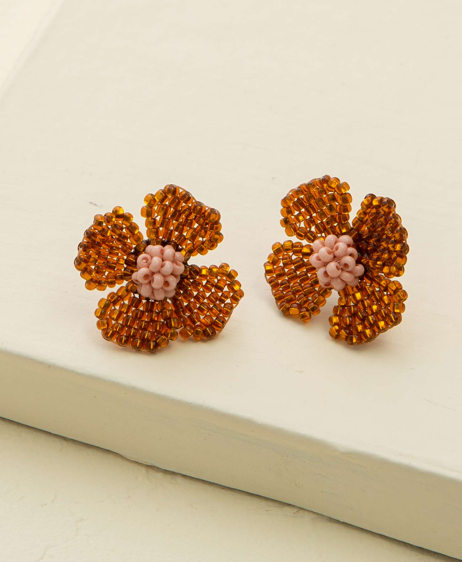 The Trellis Earrings rest on a cream-colored block. They are stud-style earrings shaped like flowers with four petals. The petals are formed from many honey-colored, transparent glass beads. The centers of the flowers are formed from a cluster of opaque, blush-colored glass beads.