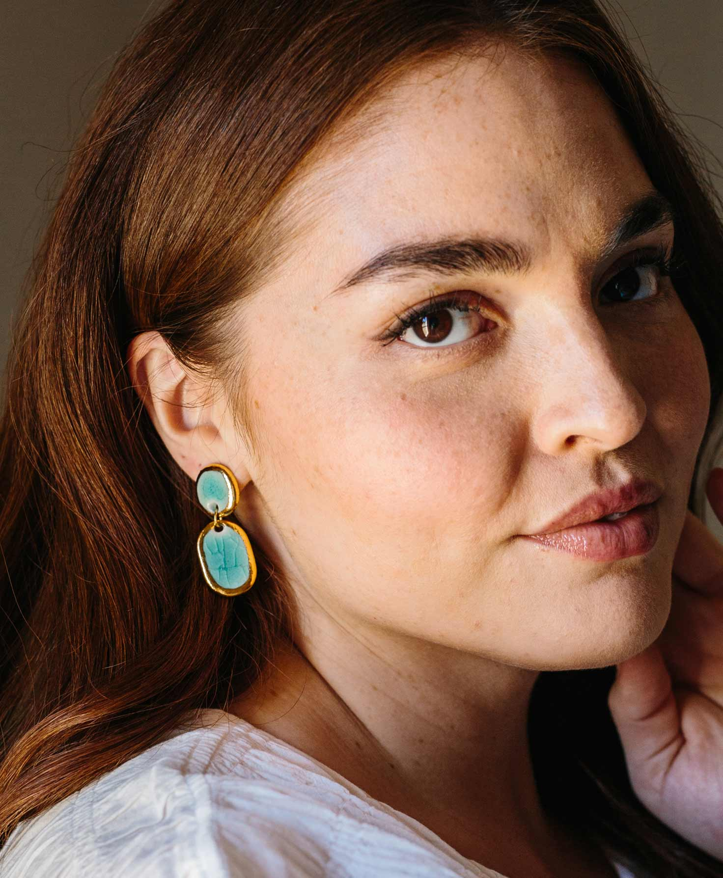 A model wears the Union Earrings paired with a classic white blouse. The porcelain glaze and gold luster on the earrings shine in the light.