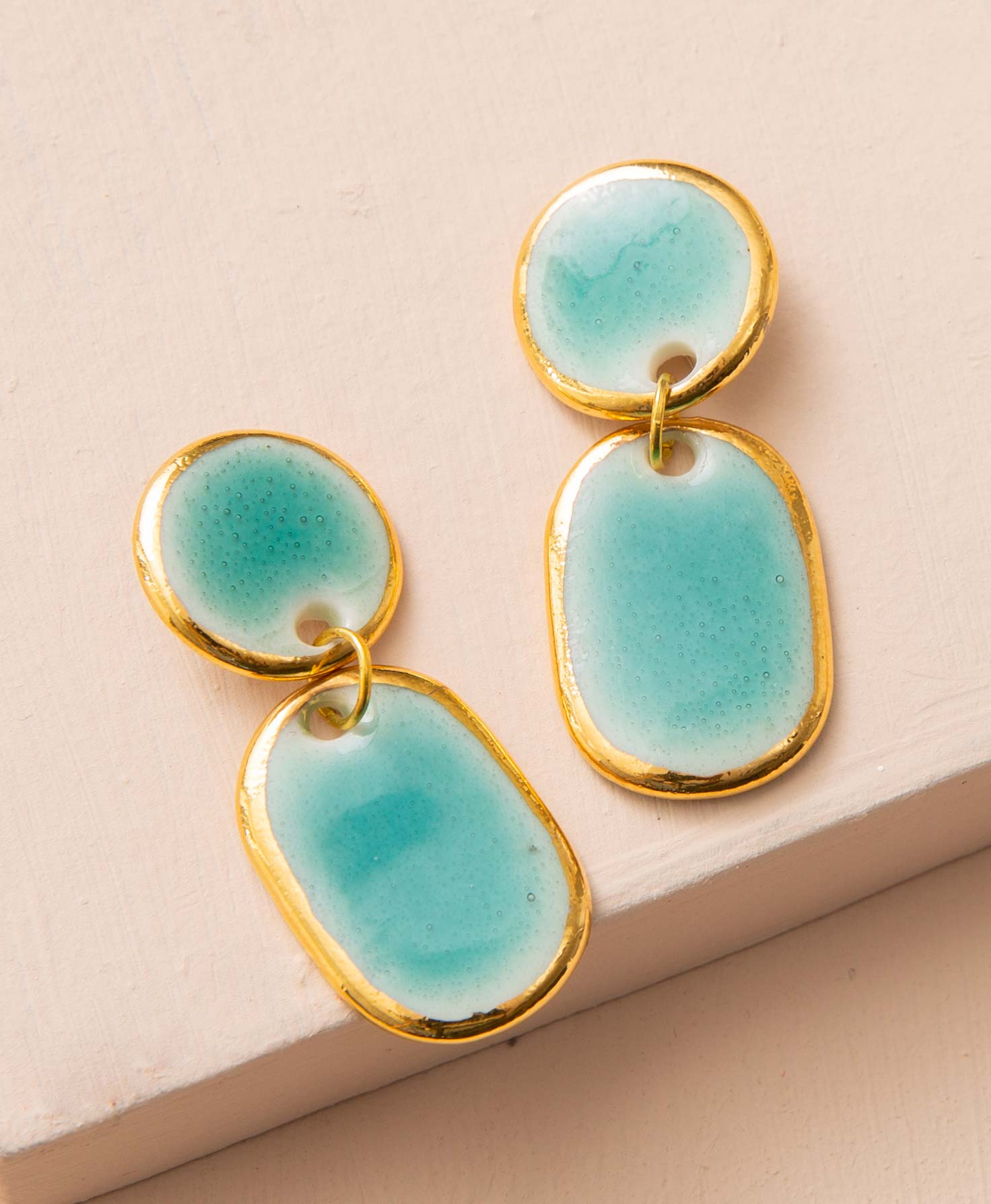 The Union Earrings rest on a blush colored block. They are stud-style earrings made of glossy porcelain. The porcelain has been finished with a teal glaze, and each earring contains unique natural variations. A flat circular disc of porcelain is connected to the ear post. Below this, an oval-shaped porcelain piece hangs down via a gold jump ring. Both of these porcelain shapes have a shining gold luster around their edges.