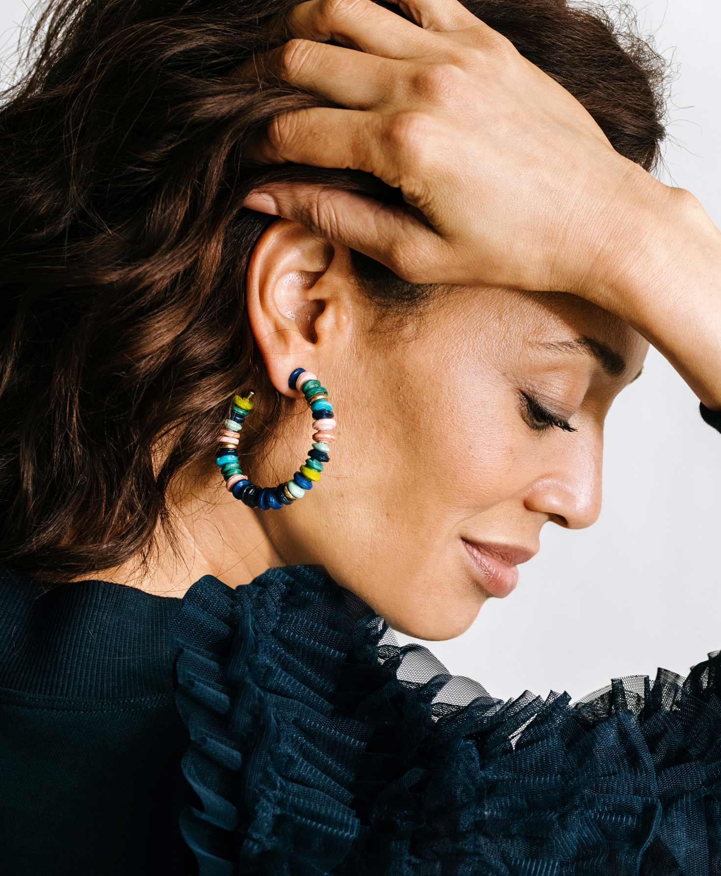 A model wears the colorful Venture Hoops. She pairs them with a deep teal blouse that plays off the oceanic colors in the earrings.