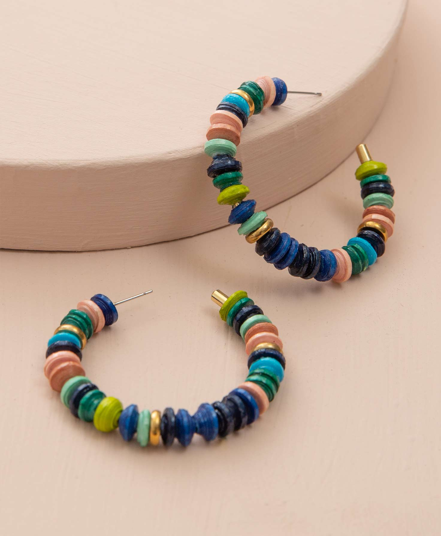 The Venture Hoops rest on a blush-colored background. Many disc-shaped paper beads are strung on the metal hoop. They are dyed shades of blue, navy, lime, mint, blush, and green. A few shiny brass discs are interspersed among the paper beads.