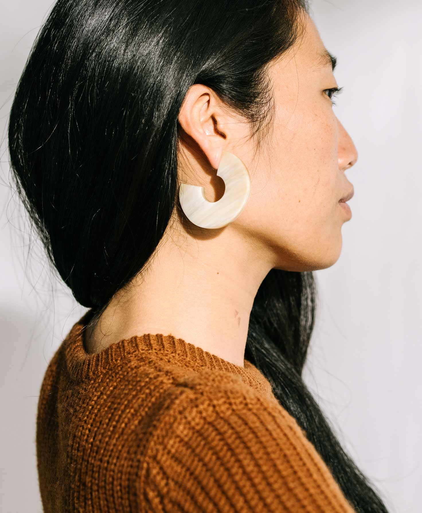 A model faces sideways, showing off the profile view of the bold Vortex Hoops. Their chunky size makes a statement, but their neutral shade tones down the look.