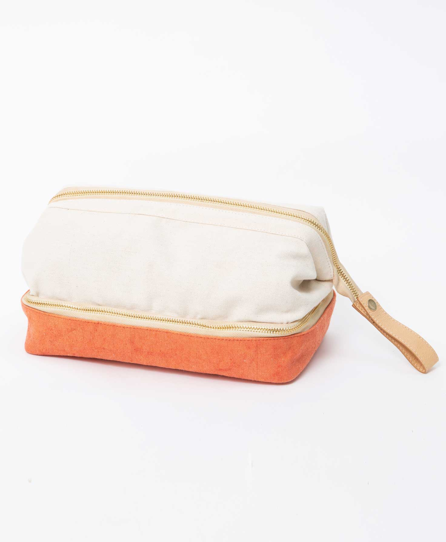 The bottom compartment of the Voyage Dopp Kit is unzipped, showing the interior of the compartment. It is lined with a smooth beige polyester lining that can easily be wiped clean. There are no interior pockets in the bottom compartment.