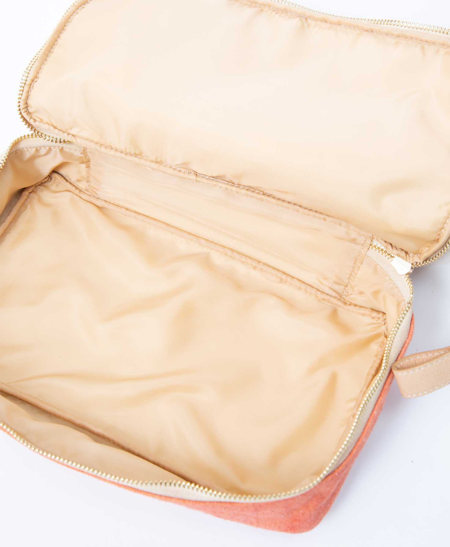 The top compartment of the Voyage Dopp Kit is unzipped, showing the interior of the compartment. It is lined with a smooth beige polyester lining that can easily be wiped clean. There are two open polyester pockets on the inside of the top compartment.