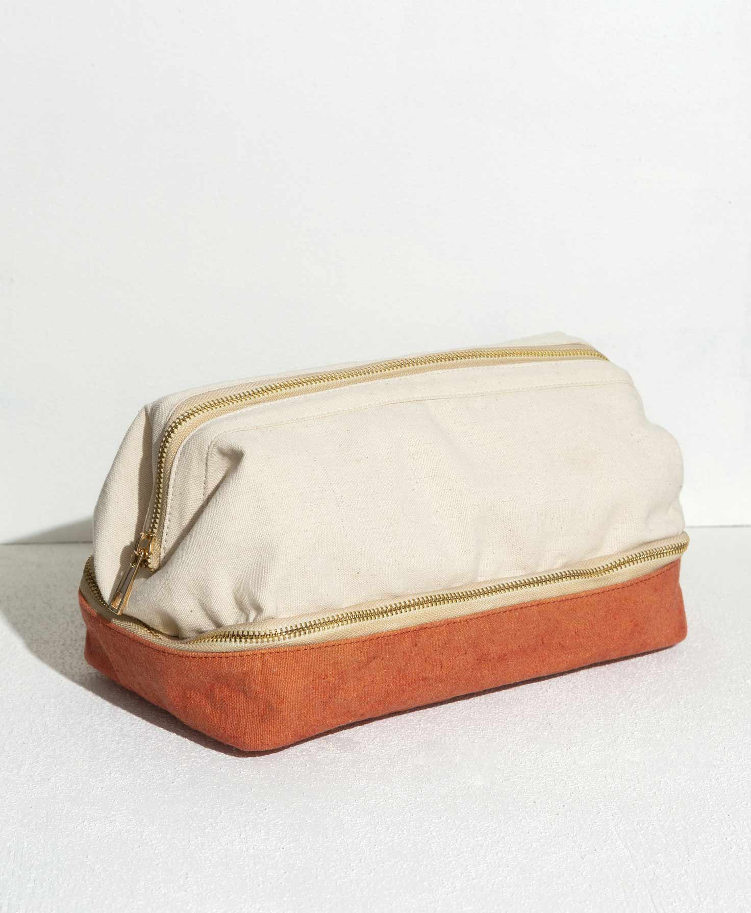 The Voyage Dopp Kit rests on a white surface. It is made of cotton canvas and features two distinct compartments. The top section is the larger of the two. It is made of cream canvas and is accessed via a brass zipper that stretches across the entire top of the bag. All along the bottom of this compartment is another brass zipper that wraps sideways around the entire bag. When unzipped, this zipper provides access to the bottom compartment, which is made of canvas in a burnt sienna shade. This compartment is flatter than the top compartment and provides additional storage.