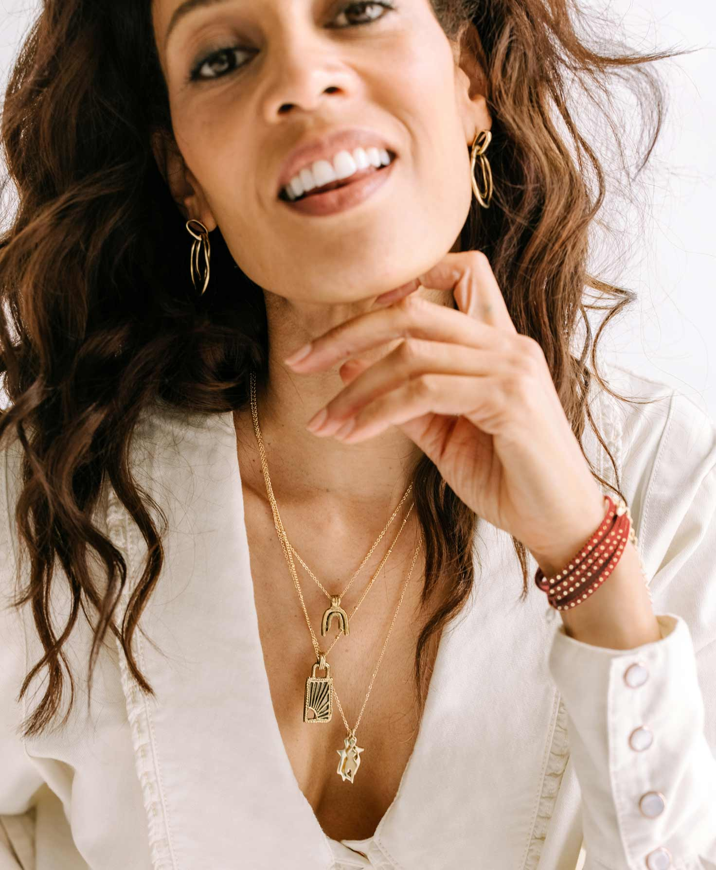 A model wears the Wild Link Earrings. She pairs them with several dainty necklaces that share the same gold and neutral color palette, including the Charmed Medallion Necklaces and the Fable Necklace.