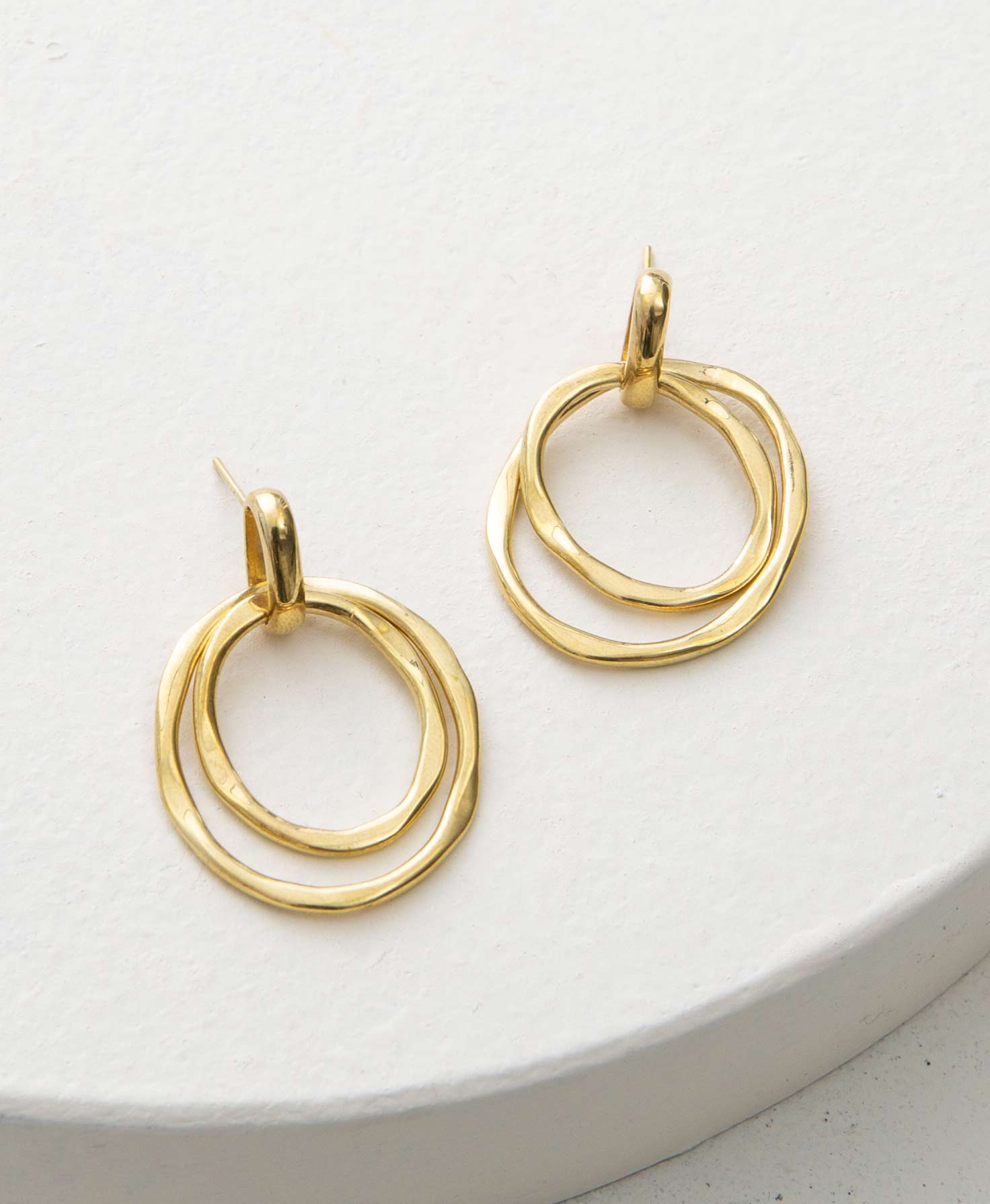 The Wild Link Earrings sit on a white block. They are post-style earrings made of shiny gold plated brass. Connected to the post is a brass loop. Hanging down from this loop is a brass hoop with a smaller brass hoop nested inside it. The hoops have an organic, hammered texture.