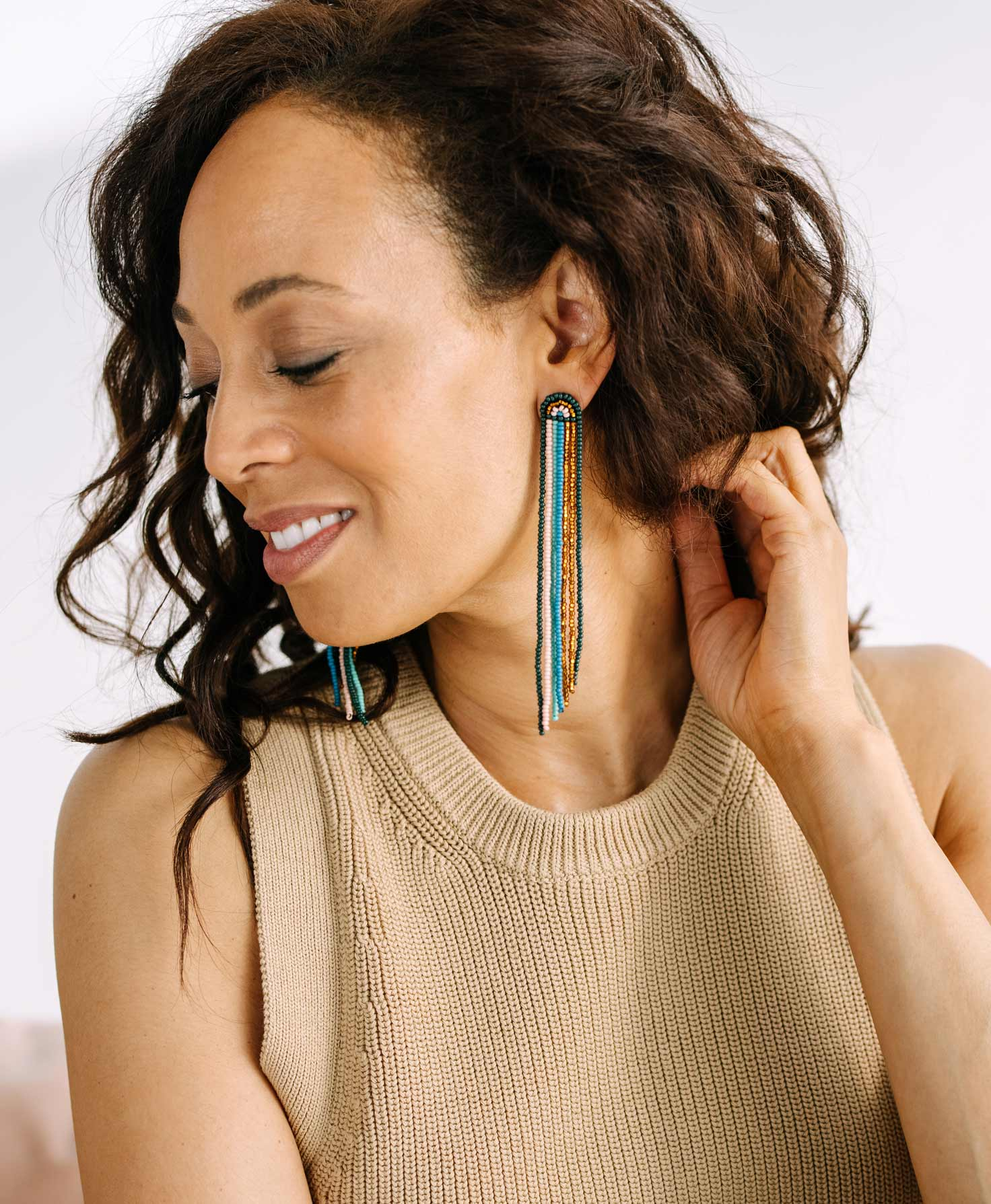 A model wears the Wonder Earrings. The long fringe of the earrings hangs down nearly the entire length of her neck. She pairs the brightly colored earrings with a simple tan top.