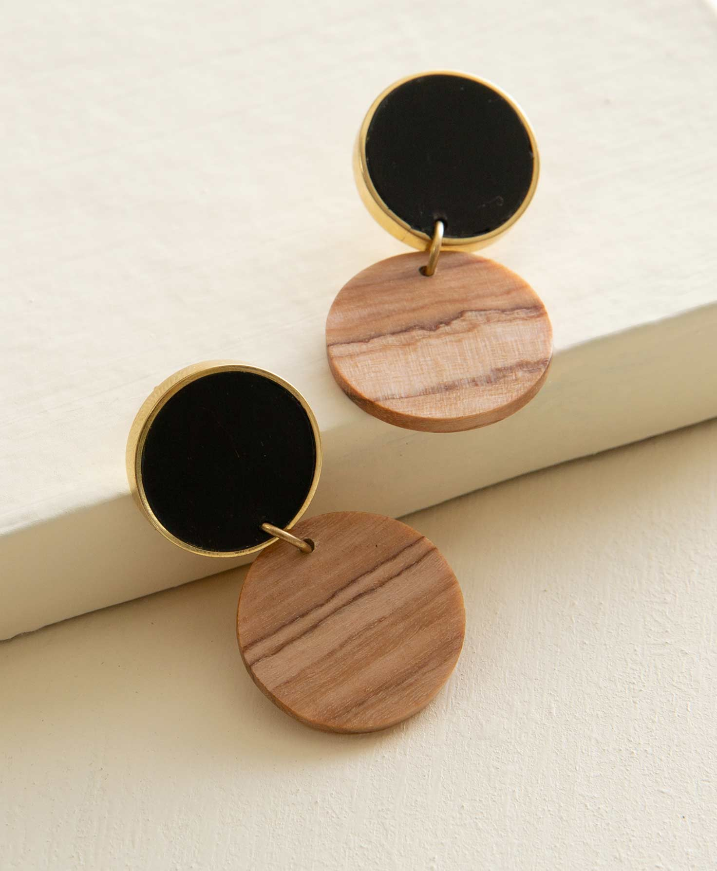 The Zeal Earrings sit propped against a cream colored block. They are post-style earrings composed of olive wood and horn. A flat circle made of matte black horn outlined in brass is connected to the ear post. Connected to this via a brass jump ring is another flat disc made of wood. The wood has a medium shade and natural markings.